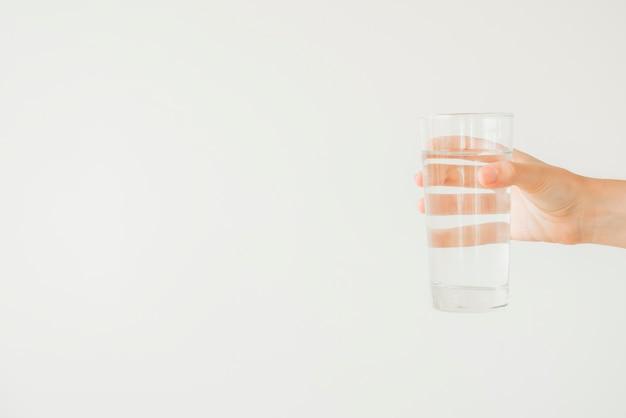 Mano che tiene il bicchiere d'acqua Foto Gratuite