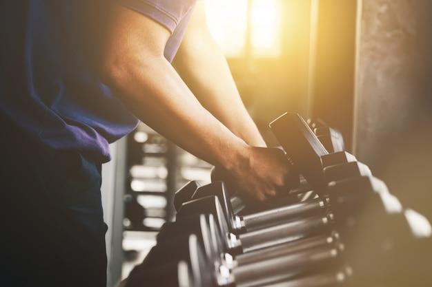 Mano che tiene il manubrio di peso in palestra vicino esercizio muscolo braccio con manubrio in metallo Foto Premium