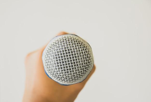 Mano che tiene il microfono su sfondo grigio. Foto Premium