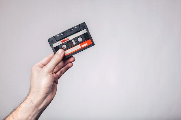 Mano che tiene il nastro a cassetta. cassetta usata. audiocassetta. Foto Premium