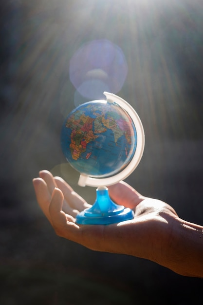 Mano che tiene il piccolo globo del mondo Foto Gratuite