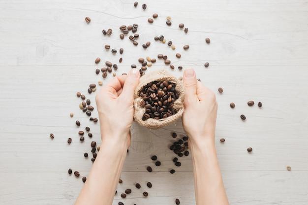 Mano che tiene il piccolo sacco con chicchi di caffè sul tavolo di legno Foto Gratuite