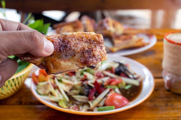 Mano che tiene il pollo alla griglia con insalata di papaya Foto Premium