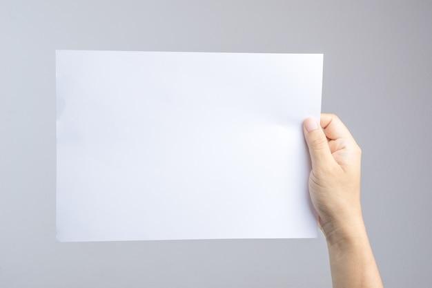 Mano che tiene la carta bianca facile sostituire con poster o brochure Foto Premium
