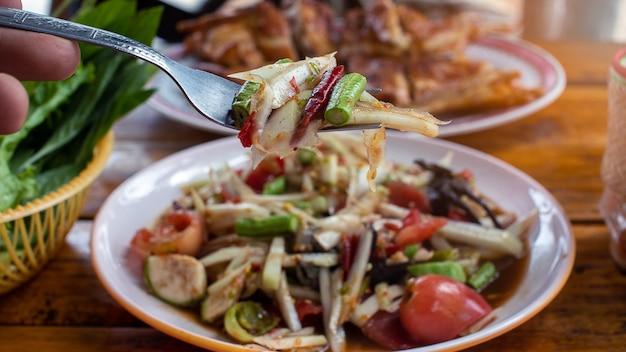 Mano che tiene la forchetta per mangiare insalata di papaya Foto Premium