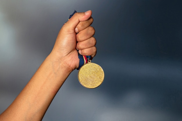 Mano che tiene la medaglia d'oro contro il cielo nuvoloso Foto Premium