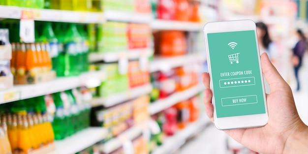 Mano che tiene smartphone con applicazione di shopping online di generi alimentari Foto Premium