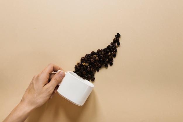 Mano che tiene tazza bianca con chicchi di caffè Foto Gratuite