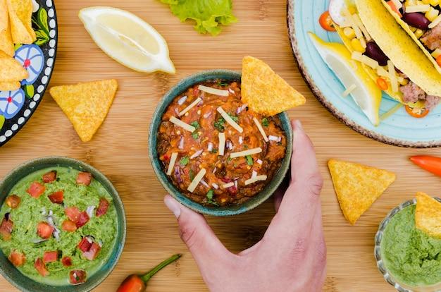 Mano che tiene tazza di guarnire con nacho vicino cibo messicano Foto Gratuite