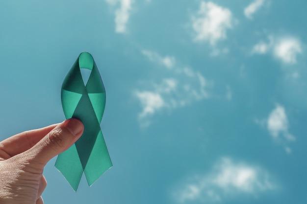 Mano che tiene teal ribbon sopra cielo blu Foto Premium