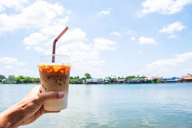 Mano che tiene un bicchiere di caffè espresso freddo con vista sul fiume e la casa. Foto Premium
