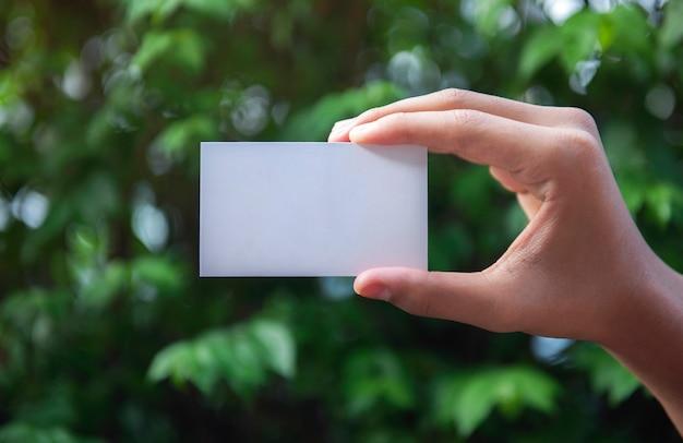 Mano che tiene un biglietto da visita bianco testo vuoto sullo sfondo della natura Foto Premium