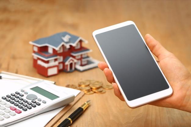 Mano che tiene un cellulare davanti al modello di casa Foto Premium