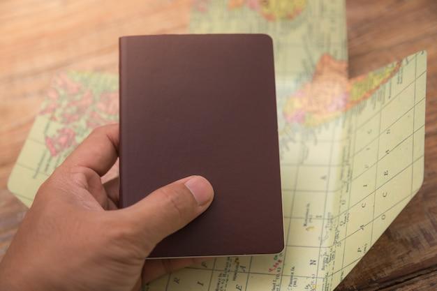 Mano che tiene un passaporto con una mappa del mondo dietro Foto Gratuite