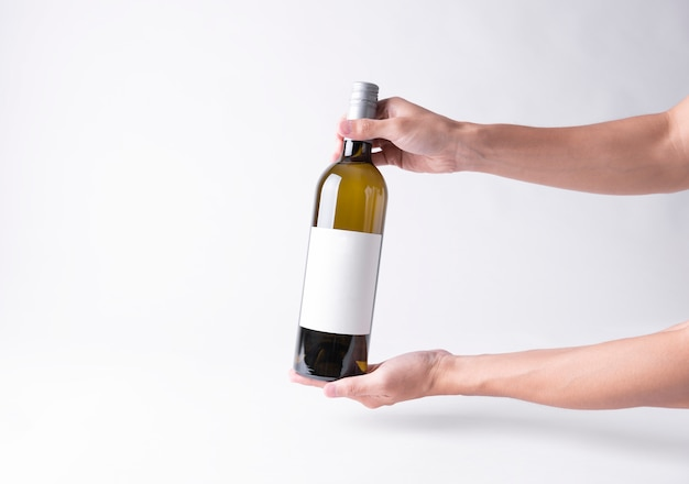 Mano che tiene una bottiglia di vino per il mock-up. etichetta vuota su uno sfondo grigio. Foto Premium