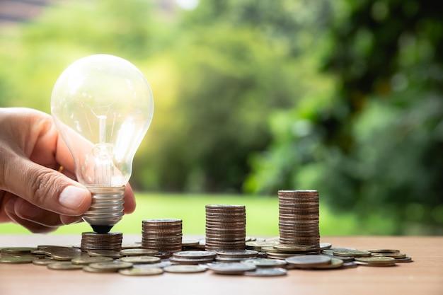 Mano che tiene una lampadina con pila di monete. Foto Premium