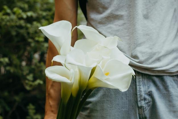 Mano con fiori di gigli di calla Foto Premium