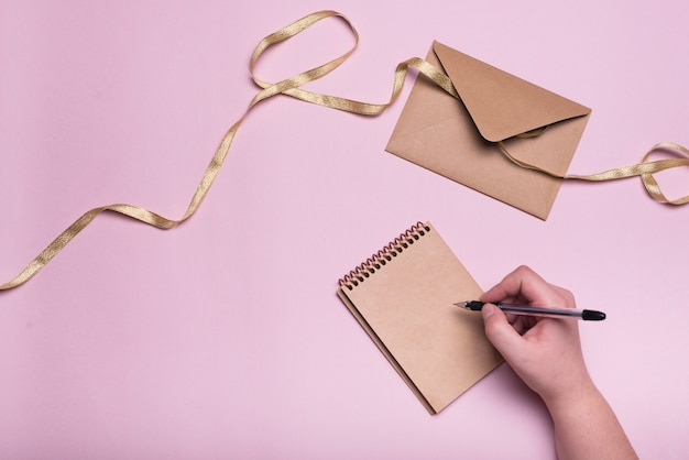 Mano con la penna vicino a notebook, busta e nastro Foto Gratuite