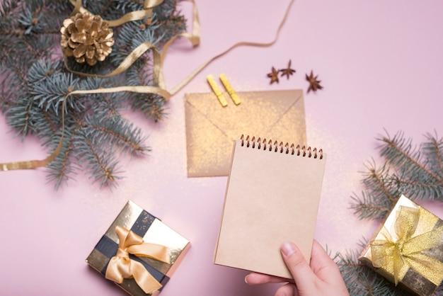 Mano con notebook vicino a scatole presenti, ramoscelli di abete, busta e nastro Foto Gratuite