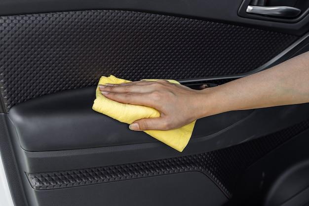 Mano con panno in microfibra per la pulizia della porta interna dell'auto Foto Premium