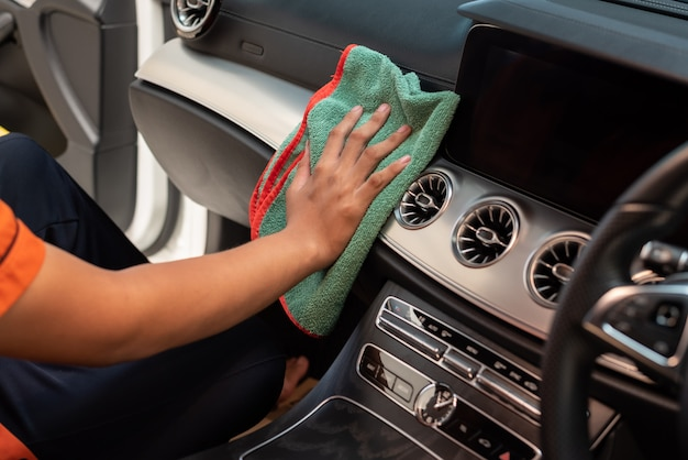 Mano con panno in microfibra per pulizia interni auto. Foto Premium