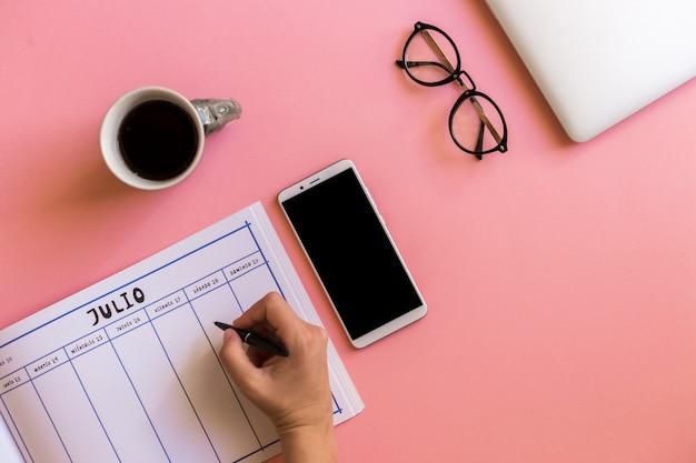 Mano con penna vicino a calendario, smartphone, tazza di bevanda e occhiali da vista Foto Gratuite