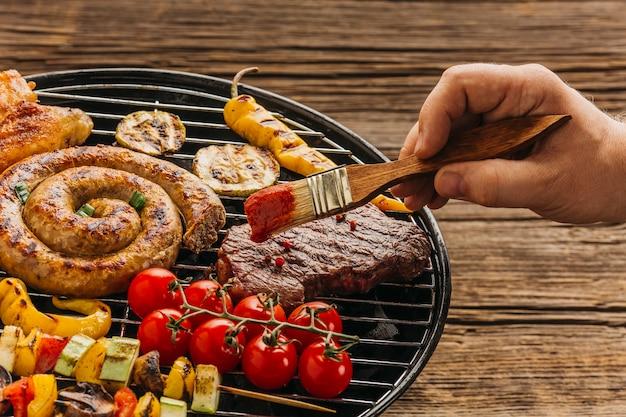 Mano con pennello da imbastitura marinare la carne sulla griglia Foto Gratuite