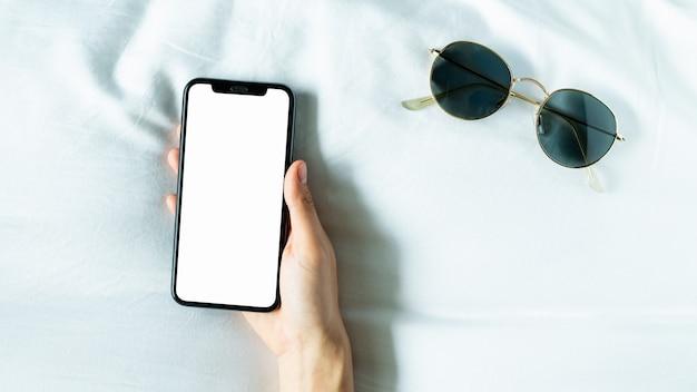 Mano con schermo vuoto dello smartphone in camera, durante il tempo libero. Foto Premium