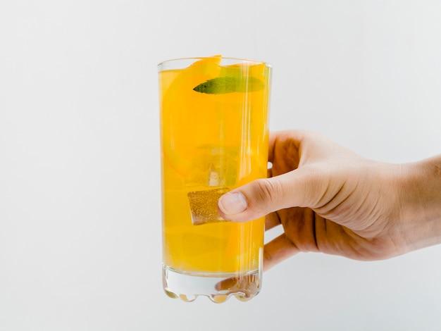 Mano con un bicchiere di succo d'arancia freddo Foto Gratuite