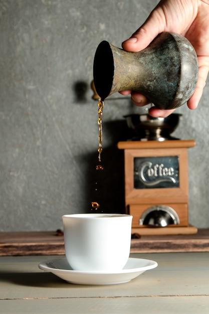 Mano degli uomini che versa una tazza di caffè che crea spruzzata Foto Premium