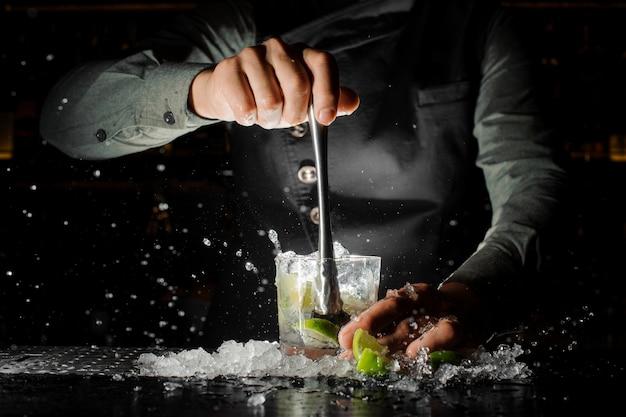 Mano del barista che spreme il succo fresco dalla calce che produce il cocktail di caipirinha Foto Premium