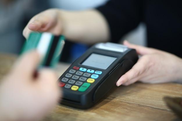 Mano del cassiere che prende la carta di credito di plastica al pagamento Foto Premium