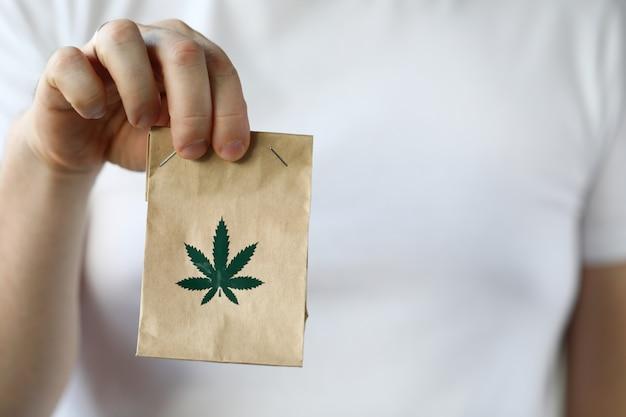 Mano del corriere che passa pacchetto con marijuana Foto Premium
