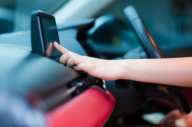 Mano del guidatore che immette un indirizzo nel sistema di navigazione o canzone radio in auto Foto Premium