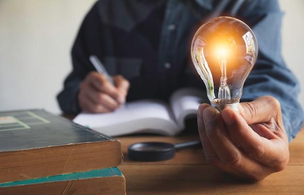 Mano del maschio che tiene una lampadina con una pila di libri Foto Premium