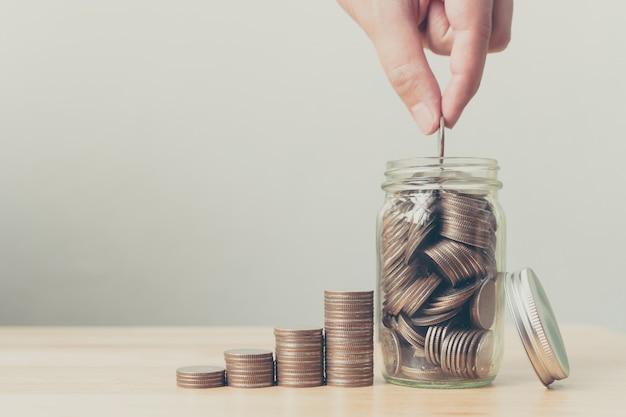 Mano del maschio o della femmina che mette le monete in vaso con soldi Foto Premium