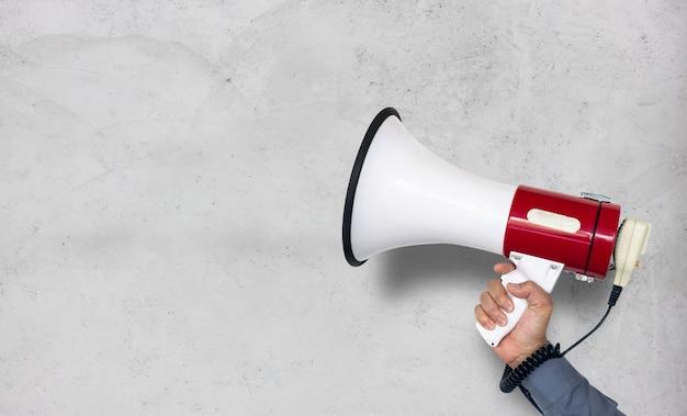 Mano del megafono della tenuta dell'uomo sul fondo bianco del muro di mattoni Foto Premium