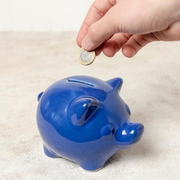 Mano del primo piano che mette una moneta in un porcellino salvadanaio Foto Gratuite