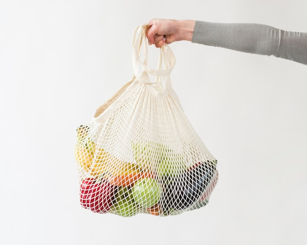 Mano del primo piano che tiene borsa riutilizzabile con frutta e verdura Foto Gratuite