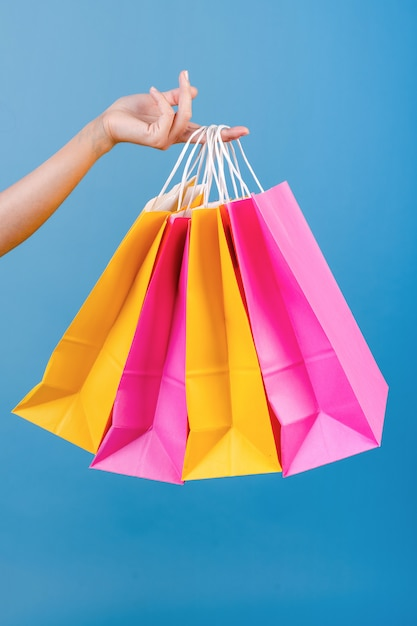 Mano del primo piano che tiene i sacchetti della spesa rosa e gialli variopinti isolati sopra il blu Foto Premium
