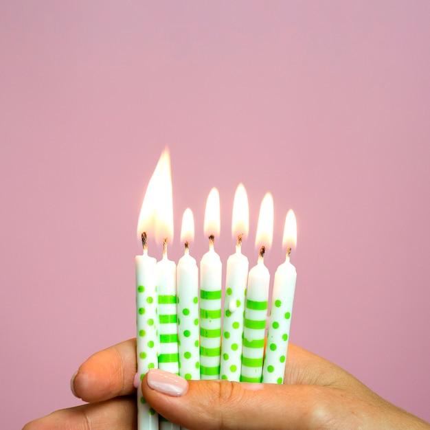 Mano del primo piano che tiene le piccole candele di compleanno Foto Gratuite