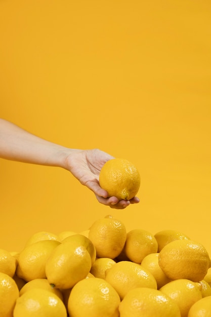 Mano del primo piano che tiene limone organico Foto Gratuite