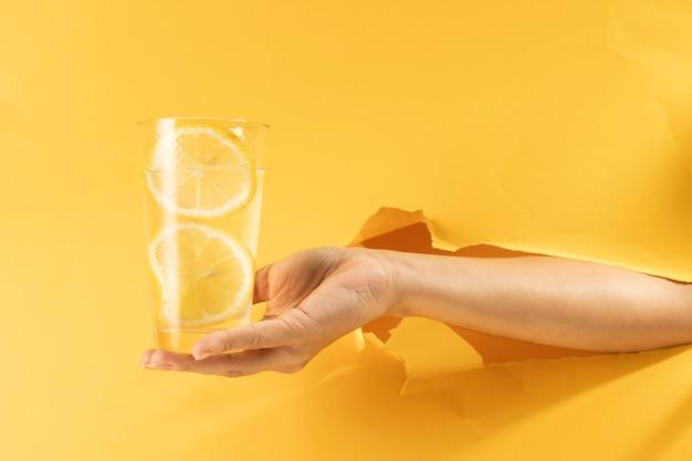 Mano del primo piano che tiene vetro di limonata Foto Gratuite