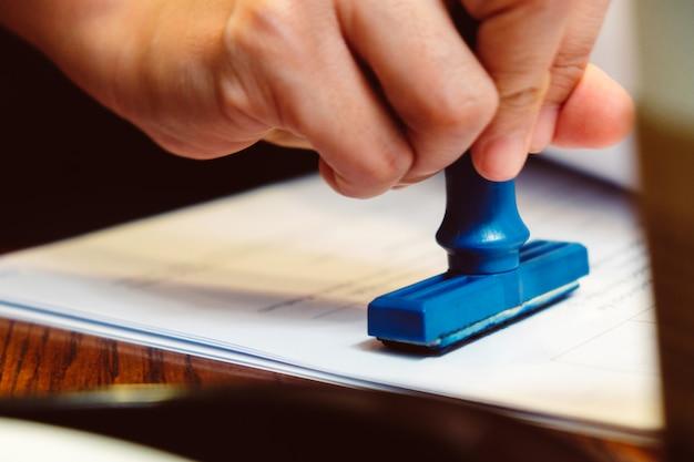 Mano del primo piano che timbra timbro di gomma sull'documenti, concetto di affari Foto Premium