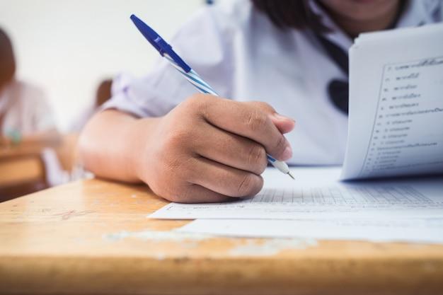 Mano del primo piano degli studenti che scrivono un esame in aula con lo sforzo Foto Premium
