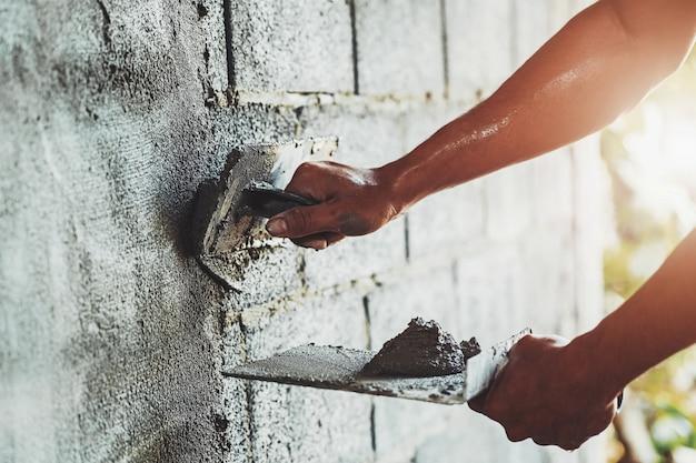 Mano del primo piano del cemento intonacante del lavoratore alla parete per la costruzione della casa Foto Premium