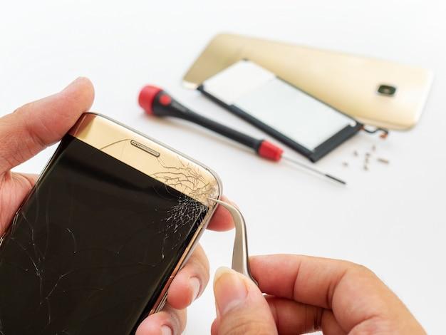Mano del tecnico che toglie lo schermo dello smartphone incrinato Foto Premium