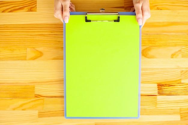 Mano dell'ufficio che tiene una cartella con una carta di colore verde sui precedenti della tavola di legno Foto Premium