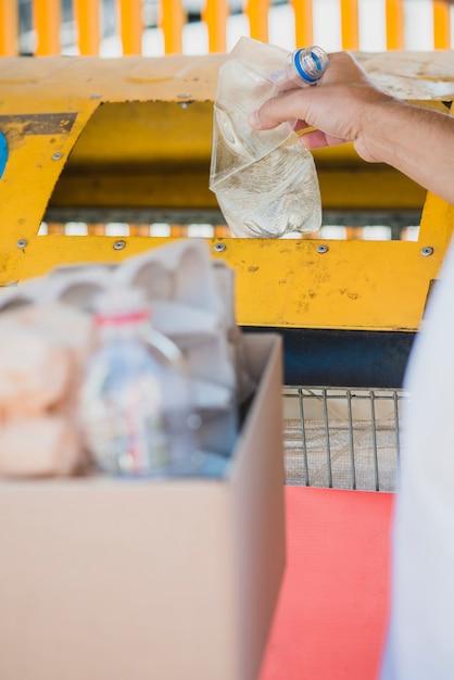 Mano dell'uomo che getta la bottiglia di plastica nel cestino Foto Gratuite
