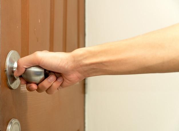 Mano dell'uomo che raggiunge la maniglia della porta aprendo la porta marrone. Foto Premium